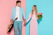 Fényképek Couple, akusztikus gitár és virág csokor, kézenfogva és néztek egymásra, a rózsaszín és a kék háttér