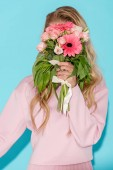 Fotografie woman in pink clothing hiding behind beautiful bouquet on blue background
