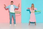 Schönes Paar blickt in die Kamera und übt mit Hula-Hoop-Reifen auf rosa und blauem Hintergrund