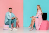 Fotografie couple sitting on big macaroon and nail polish models while looking at camera on pink and blue background