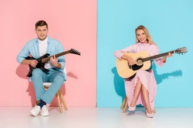 couple sitting on chairs, playing electric and acoustic guitars while looking at camera on pink and blue background