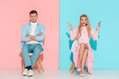 man with arms crossed and excited woman with hands in air sitting on chairs on pink and blue background