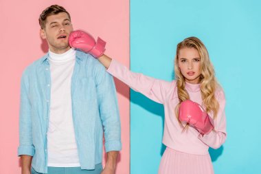 angry woman in boxing gloves hitting man in face on pink and blue background