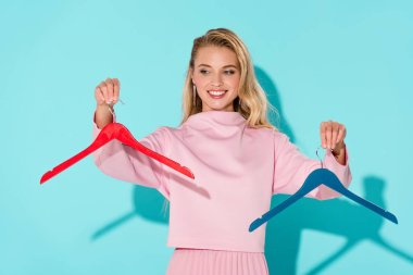beautiful smiling woman holding empty clothes hangers on turquoise background