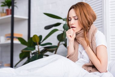 sick woman coughing and touching throat at home