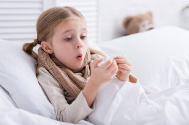 shocked sick child with scarf over neck lying in bed and checking temperature with thermometer at home
