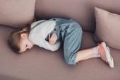 vysoký úhel pohled na nemocné dítě s bolestí žaludku ležel na pohovce v obývacím pokoji