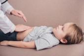 Oříznout obrázek pediatrist nahmatáním nemocný žaludek na pohovce v obývacím pokoji