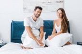 Photo young attractive couple sitting in bed with white pillows