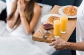 oříznutý pohled člověka drží Dřevěný tác s pomerančovým džusem a croissanty
