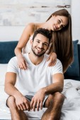 young attractive girl hugging cheerful man while sitting on bed