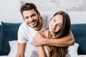 Fotografie mladý šťastný muž objímání přítelkyni a vesele