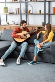 young handsome man playing guitar for girlfriend in living room