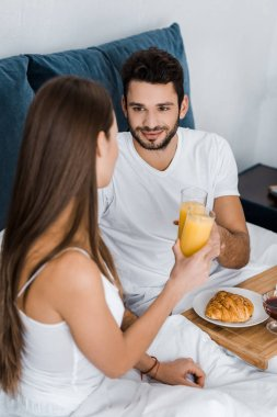 handsome man looking at girlfriend and clinking with glasses of orange juice