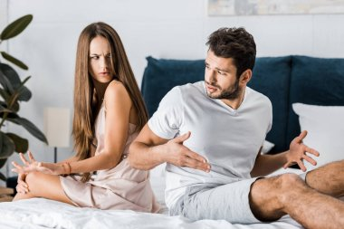 unhappy frustrated couple in pajamas sitting on bed back to back and gesturing angrily, sexual problems concept