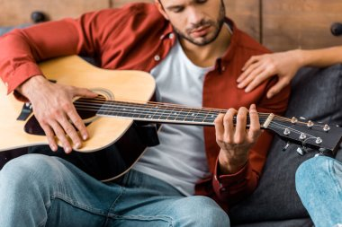 cropped view of young handsome man playing acoustic guitar while sitting on sofa