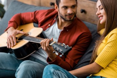 cropped view of man sitting on sofa and playing guitar for smiling girlfriend