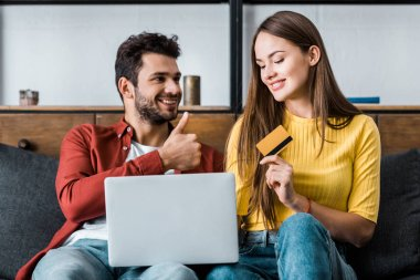 happy woman holding credit card while boyfriend showing thumb up sign