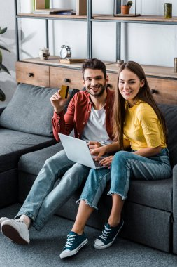 cheerful boyfriend and girlfriend doing online shopping on sofa in living room