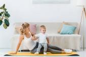 Fotografie Žena odpočívá se synem na fitness mat doma