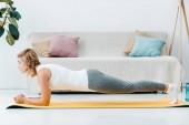 atraktivní žena v sportovní dělá prkno na žluté fitness mat v obývacím pokoji