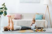 asszony feküdt a szőnyegen, és súlyzók és aranyos totyogó fiú tarka Fakockák nappaliban ül gyakorlása
