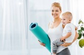 beautiful woman holding blue fitness mat and smiling cute toddler boy