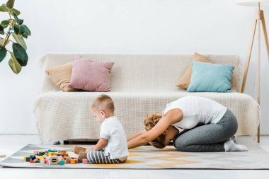 woman doing stretching exercise on carpet and toddler boy playing with multicolored cubes near couch at home