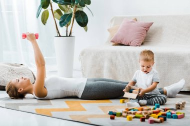 attractive woman lying on carpet and exercising with dumbbells and cute toddler boy holding wooden box with multicolored cubes in living room