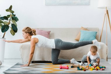 woman exercising near couch and toddler boy playing with multicolored wooden cubes on carpet in living room