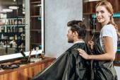 Kadeřník se usmívá na kameru při stříhání vlasů na pohledný mladý muž v salonu krásy