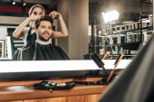 reflection in mirror of young hairdresser cutting hair to handsome smiling man in beauty salon