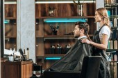 side view of female hairstylist and handsome young man looking at mirror in beauty salon