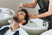 Oříznout záběr profesionální kadeřník mytí vlasů mužského klientovi v salonu krásy