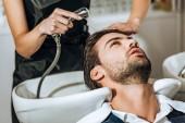 částečný pohled kadeřnice mytí vlasů pohledný mladý muž klientovi v salonu krásy
