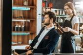 fiatal női fodrász gazdaság haj szárító és keres a jóképű férfi ügyfél szépségszalon