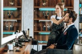 beautiful young hairdresser doing hairstyle to handsome client and looking at mirror in beauty salon