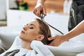 částečný pohled kadeřník mytí vlasů na atraktivní mladá žena v salonu krásy