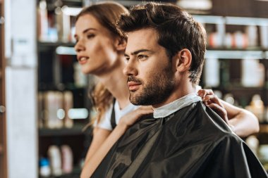 handsome young man and beautiful female hairstylist looking away in beauty salon