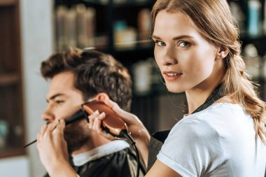 attractive hairstylist looking at camera while trimming hair to male client in beauty salon