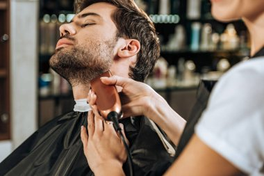 cropped shot of hairdresser trimming beard to handsome client in beauty salon