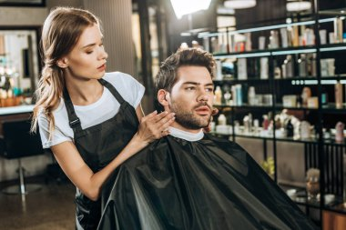 beautiful young hairdresser doing hairstyle to handsome male client in beauty salon