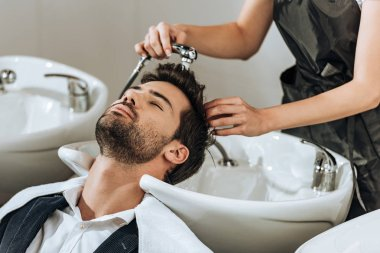 cropped shot of professional hairstylist washing hair to male client in beauty salon