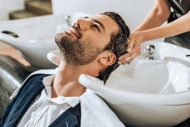 partial view of hairstylist washing hair to handsome smiling man in beauty salon
