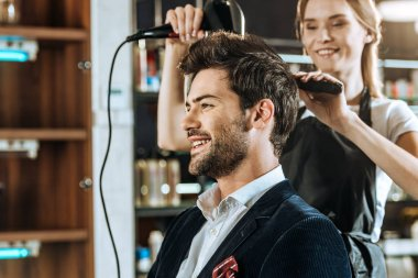 smiling young hairstylist drying hair to handsome happy man in beauty salon