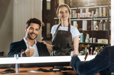 beautiful hairdresser standing near handsome smiling client showing thumb up in beauty salon