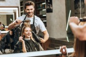 smiling young hairstylist combing and drying hair to happy young woman in beauty salon