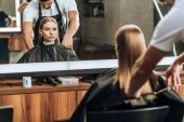 hairstylist cutting hair to beautiful young woman in beauty salon