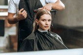 oříznuté záběr kadeřník pomocí žehličky a při pohledu na zrcadlo v salonu krásy dívka