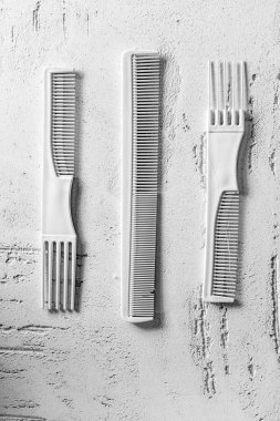 close-up view of various decorative combs on wall in beauty salon